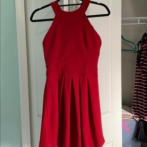 Red bow-back halter neck dress with pleated skirt